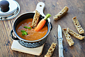 Carrot soup with bread sticks