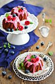 Drei Mini-Gugelhupfe mit roter Bete, Zuckerguss, Zuckerblumen, frischen Heidelbeeren und Minze