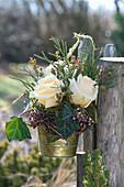 Kleiner Strauß mit Rosen am Gartenzaun aufgehängt