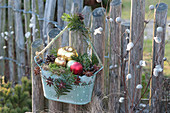 Jardiniere weihnachtlich geschmückt am Gartenzaun