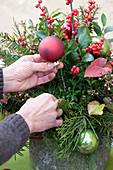 Weihnachtsgesteck mit Koniferenzweigen und Christbaumkugeln
