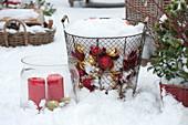 Korb mit Christbaumkugeln und Windlicht im Schnee