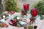 Weihnachtliche Tischdeko mit Kiefer, Hagebutten und Zieräpfeln