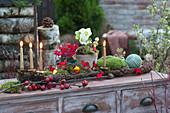 Weihnachtliche Dekoration mit goldenen Kerzen auf Rinde