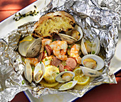Seafood cooked in foil with corn on the cob and grilled bread