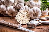 Knoblauchknollen, ganz und halbiert, Knoblauchpresse und Messer auf Holzuntergrund
