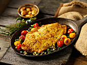 Breaded tilapia fillet with cherry tomatoes