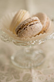 Various macarons in paper cups and a glass bowl