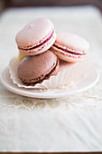 Various French macarons in a paper cup on a small plate
