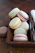 Various colourful macarons in a wooden box