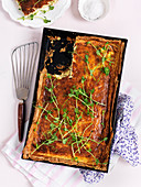 Cheese quiche in a metal baking tray sprinkled with pea sprouts (top view)