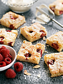 Sheet cake with almonds and raspberries, sliced