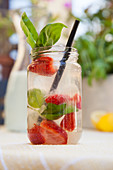 Lemonade with strawberries and basil outdoors