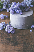 Layer cake with lilac blossom, on a rustic wooden surface