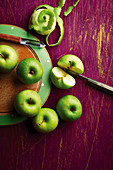 Green apples peeled, cut and whole, with knife and peeler on a chopping board