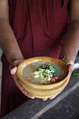 Person hält Schälchen mit Eiersuppe (Indien)
