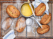 Several stollen with melted butter and powdered sugar on a cooling rack