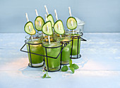 Cucumber and lime smoothies with mint in glasses in a cup holder