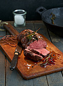 Beef fillet with rosemary on a rustic wooden board