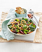 A mixed leaf salad with bacon and fried onion rings