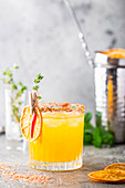 Refreshing summer citrus cocktail with orange, lemon juice and ice in a glass over gray background