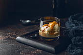 Ice cream with caramel topping and Irish cream liqueur in a glass over dark background