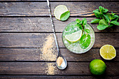 Refreshing mint cocktail mojito with rum and lime, cold drink or beverage with ice on white wooden background