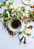 Green cup of tea with blossom on the table and cutlery