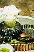 Green matcha latte in a little glass on baking trays
