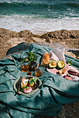 A picnic at the sea with bread and avocado