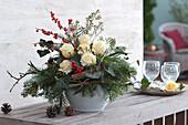 Winterstrauß mit Rosen, Koniferen-Zweigen und roter Winterbeere