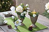 Kleine Sträuße aus Rosen, Christrosen und Tanne in silbernen Bechern