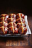 Chocolate hot cross buns with spelt on a cooling rack (vegan)