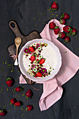 A yoghurt bowl with wholemeal oats, strawberries, pistachios and pomegranate