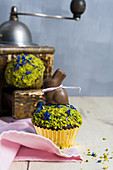 A chocolate muffin topped with chopped pistachios and a chocolate bunny