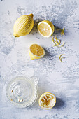 Peeled lemons and juicer, light background
