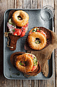 Bagels with salmon fish, cream cheese, cucumber and fresh radish slices on metallic tray on rustic gray wooden background