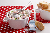 Spicy soused herring and pasta salad with slices of baguette