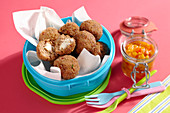 Party meatballs with pepper and papaya chutney and plastic cutlery