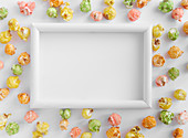 A white frame with colourful popcorn