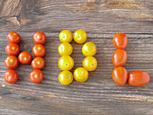HDL spelled out in tomatoes on a wooden board
