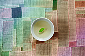 Green tea with a leaf in a small bowl