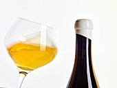 Natural wine in a glass and a bottle (orange wine)
