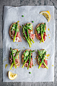 Slices of grilled ciabatta with crushed peas, ham and asparagus