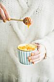Frau süsst Kurkuma-Latte (Goldene Milch) mit Honig