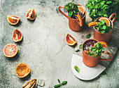 Blood orange Moscow mule alcohol cocktails with fresh mint leaves and friots and ice in copper mugs