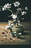 Traditional Asian tea ceremony arrangement with golden iron teapot, cups, candles and almond blossom flowers
