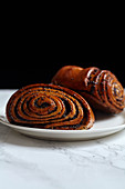 Close up side image of sweet rolls with poppy seeds on marble table