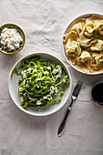 Traditional italian ravioli with ricotta cheese and spinach tagliatelle served with a glass of red wine