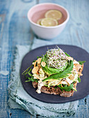 A slice of whole meal bread topped with Chinese cabbage, avocado and beansprouts